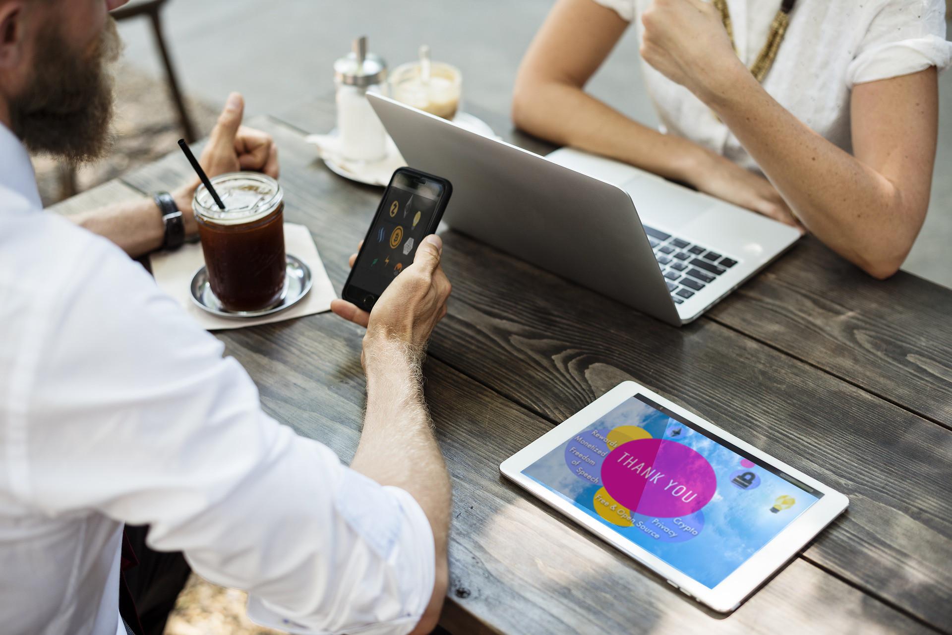 Personen sitzen an einem Tisch, auf dem digitale Geräte liegen
