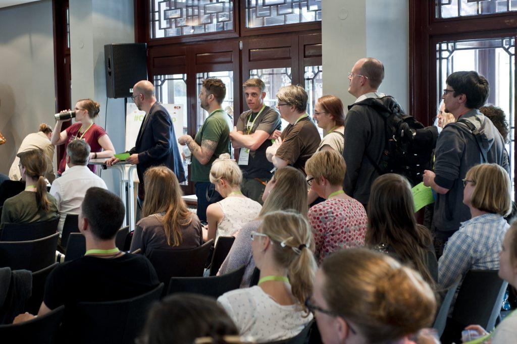Personen stehen für die Sessionplanung beim OERcamp an