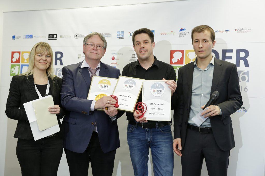 OER-Award 2016 in der Kategorie Schule für Zentrale für Unterrichtsmedien im Internet e.V.. Weitere Nominierte: segu Geschichte und ZUM.de v.l.n.r. Laudatorin Gabi Netz (Lehrer-Online), Karl-Otto Kirst (ZUM-Wiki), Dr. Christoph Pallaske (segu Geschichte), Laudator Simon Köhl (Serlo).