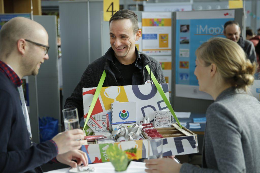 Der Mann mit dem Bauchladen verteilt Give-Aways der Veranstaltungspartner, z.B. Wikimedia Deutschland und bpb