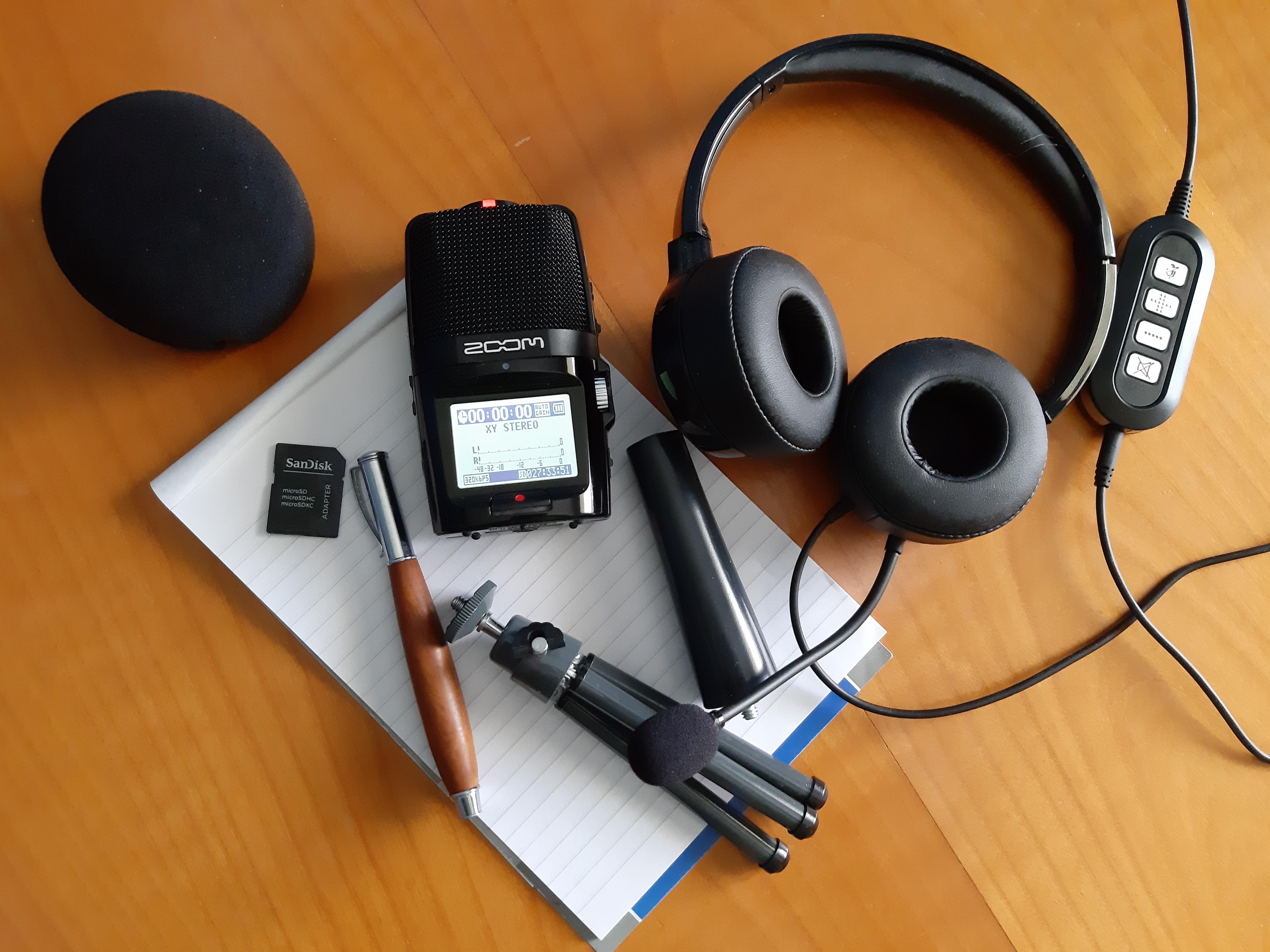 Bild zeigt Zoom-Aufnahmegerät, Headset, Stativ, Speicherkarte, Schreibblock und Stift