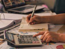 Mensch überträgt Zahlen von Taschenrechner in Kalender