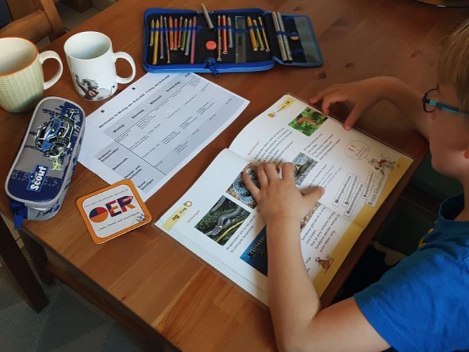 Kind mit Schulheften und Büchern an einem Tisch